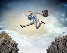 Performance Management Gap Young businessman jumping over gap