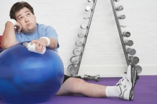 Portrait of a wistful health club member sitting on floor with exerc
