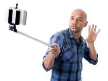 Young Hispanic Man In Casual Shirt Having Fun Shooting Mobile Ph