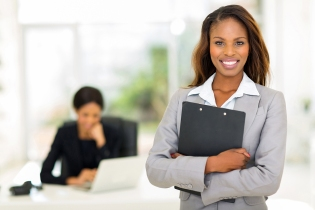 black business woman holding clipboard with colleague on backgro