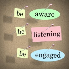 Be Aware, Listening and Engaged words on papers pinned to a bull