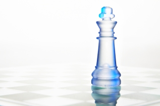 transparent glass chess queen on chessboard