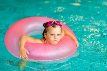 Funny Little Girl In Pink Goggles In The Swimming Pool