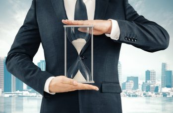 Businessman Holding Hourglass At Megapolis City Background, Time