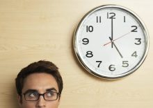 Young businessman wearing spectacles looking at clock on wooden