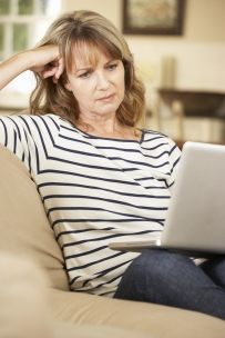 Puzzled Mature Woman Sitting On Sofa At Home Using Laptop